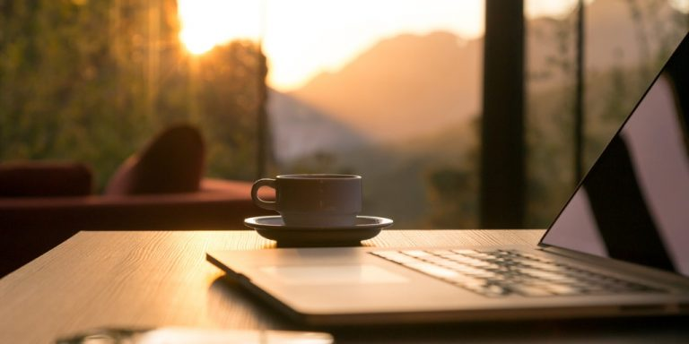 coffee cup and laptop on wooden table outside with almost sunset lighting and mountain in distance